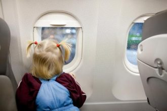 child in airplane looking at the window